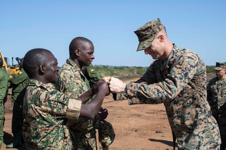 A U.S. and Ugandan service member fist-bump while others stand by.