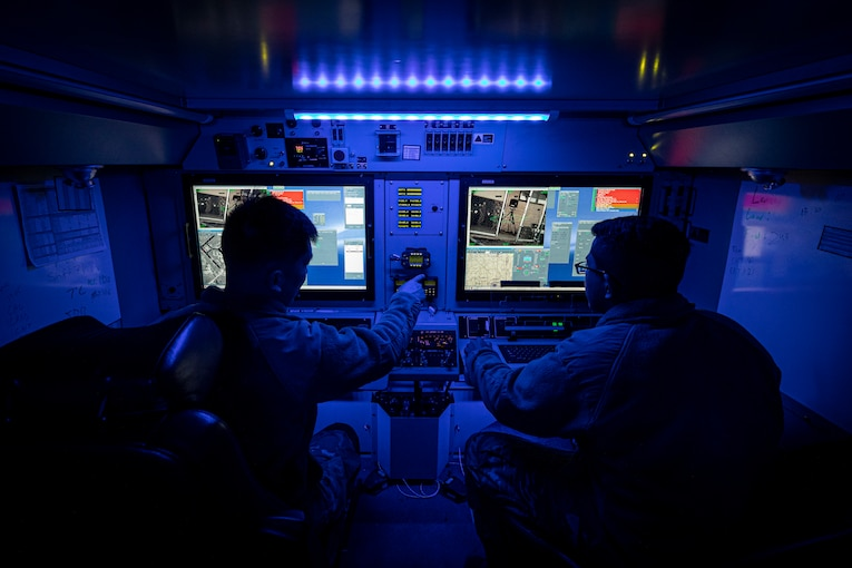 Soldiers sit in front of computer screens in an area illuminated by blue light.