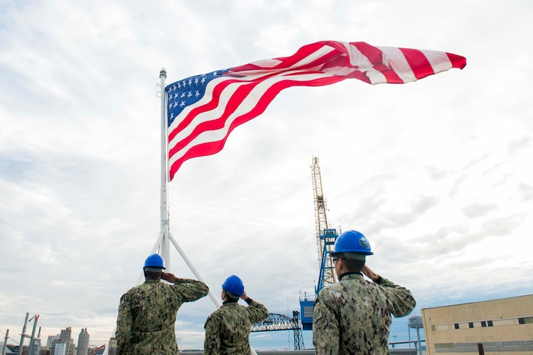 Sailors wearing blue helmets salute an American flag.