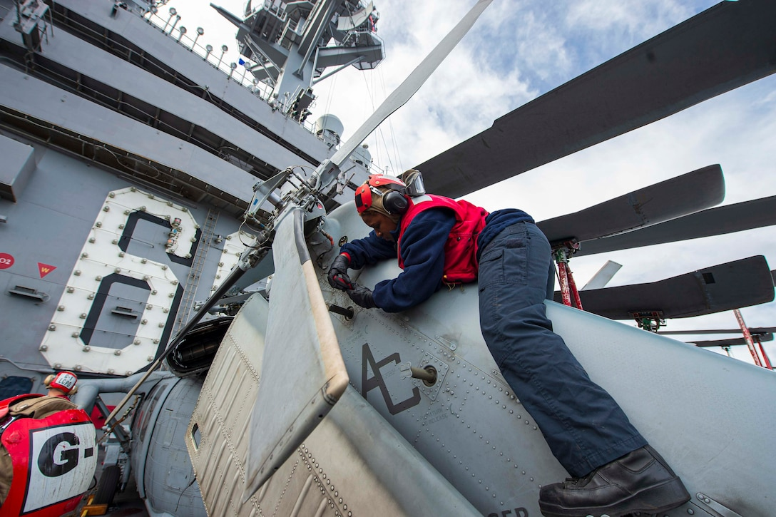 A sailor works on the side of a helicopter.