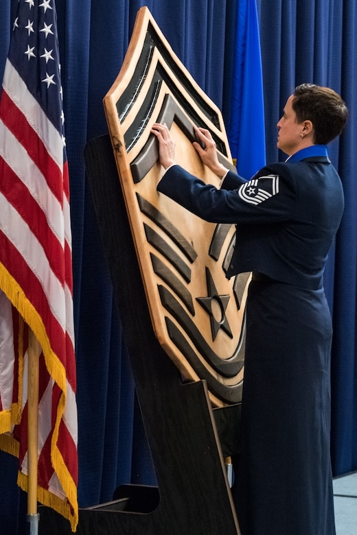 Senior Master Sgt. Georgette Springs, Air Force Mortuary Affairs Operations operations division superintendent, places the master sergeant chevron on the wooden chief's insignia display during the Chief Master Sergeant Recognition Ceremony at the Landings, Feb. 8, 2020, on Dover Air Force Base, Del. Springs is a chief master sergeant select. (U.S. Air Force photo by Roland Balik)