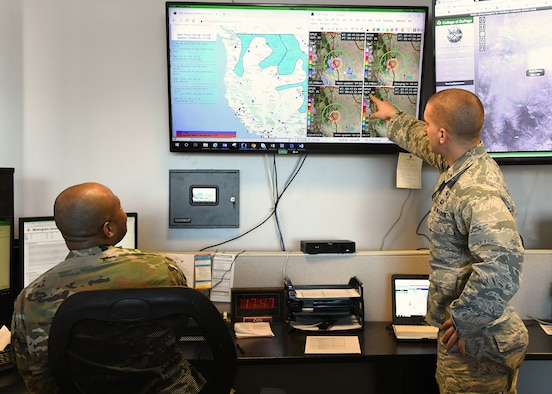 1st Lt. Travis Hodos, 21st Operations Support Squadron weather flight commander, and Master Sgt. Jonathon Winston, 21st OSS weather flight chief, analyze weather forecasts, Jan. 5, 2020 in anticipation of a snow call on Peterson Air Force Base, Colorado. The 10-person weather flight monitors weather conditions around the clock to provide the most accurate and up-to-date information to base leadership. (U.S. Air Force photo by Erica Blanton)