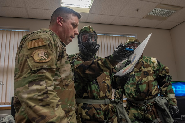 Master Sgt. James McGarvey, 100th Civil Engineer Squadron emergency management section chief, discusses chemical, biological, radiological, nuclear and explosive procedures during a readiness exercise at RAF Mildenhall, England, Feb. 10, 2020. The main purpose of the exercise was to demonstrate how rapidly Bloody Hundredth Airmen are able to organize an entire wing and deal with simulated real-world scenarios. (U.S. Air Force photo by Staff Sgt. Luke Milano)