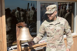 Spc. Cameron Insinga, watercraft operator, 492nd Theater Harbormaster Operations Detachment (THOD), rings the bell eight times to signify mission complete during the 492nd THOD's end of mission ceremony at Kuwait Naval Base, Feb. 13, 2020.
