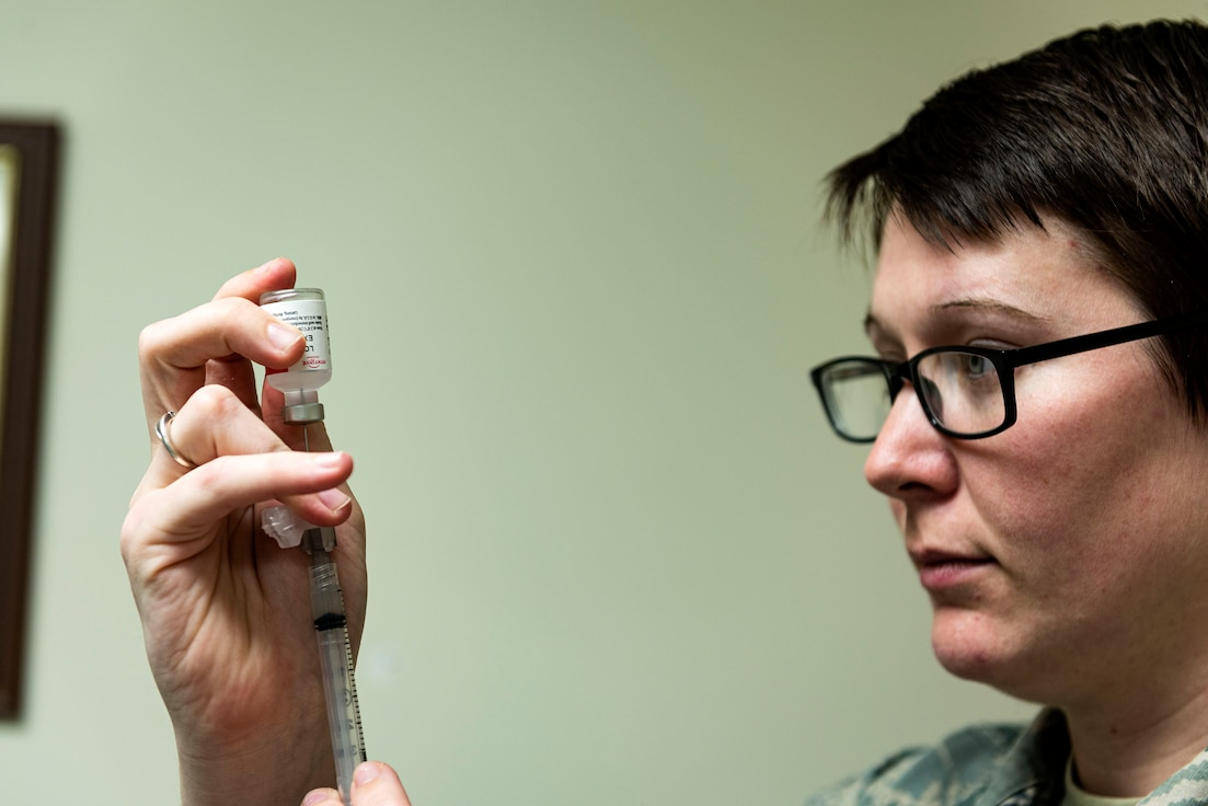 Photo of an immunizations technician drawing vaccination fluid.
