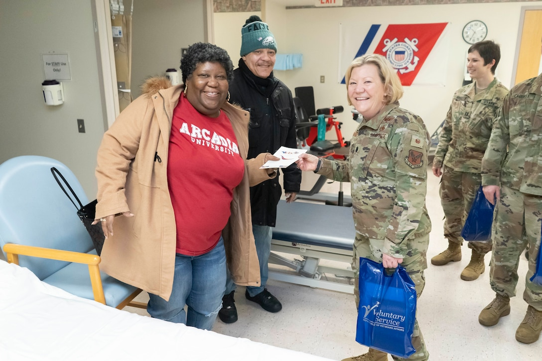 Air Force Lt. Col. Susan McMullen, a DLA Troop Support project manager, right, hands a veteran patient a Valentine's Day card at the at the Corporal Michael J. Crescenz Veterans Affairs Medical Center, Feb. 10, 2020 in Philadelphia.
