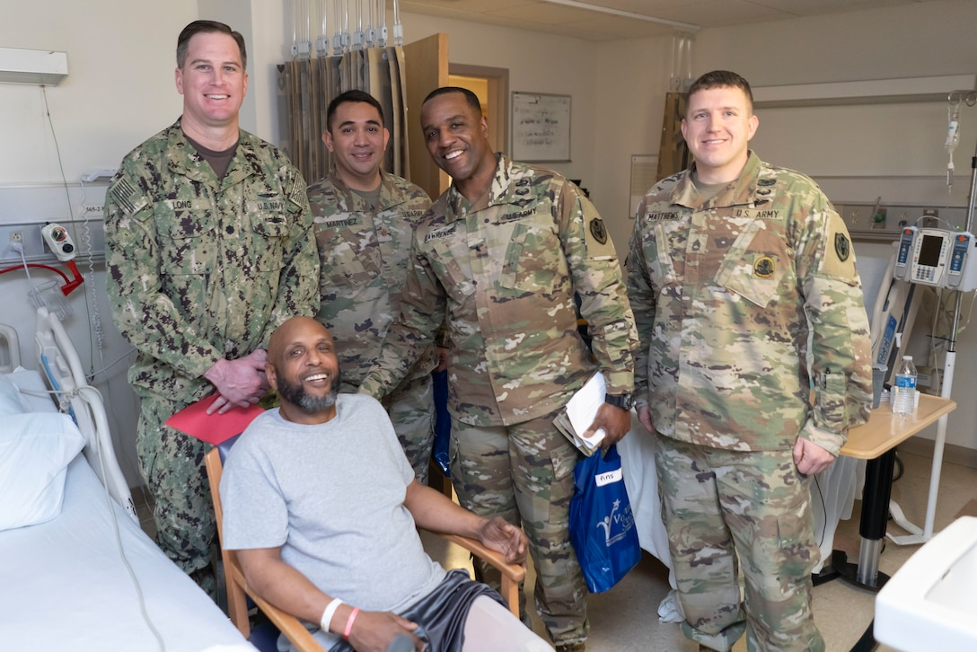 Military members of DLA Troop Support pose with a veteran patient at the Corporal Michael J. Crescenz Veterans Affairs Medical Center, Feb. 10, 2020 in Philadelphia.