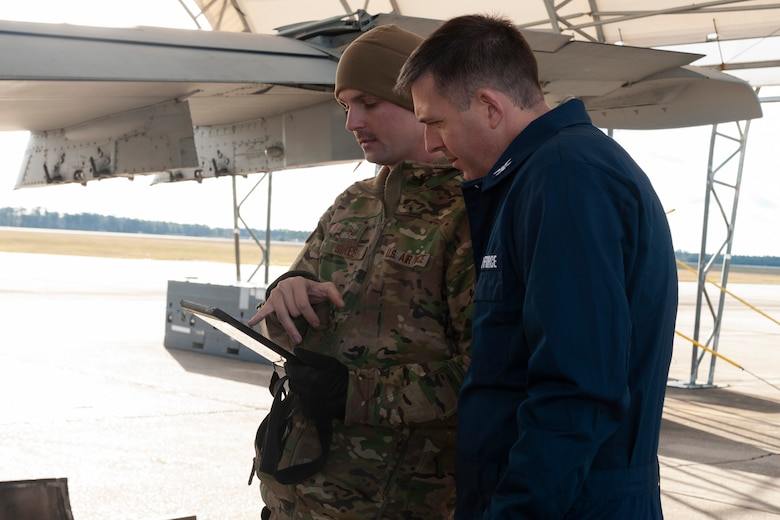 Photo of Airman explaining a technical order to Col. Walls