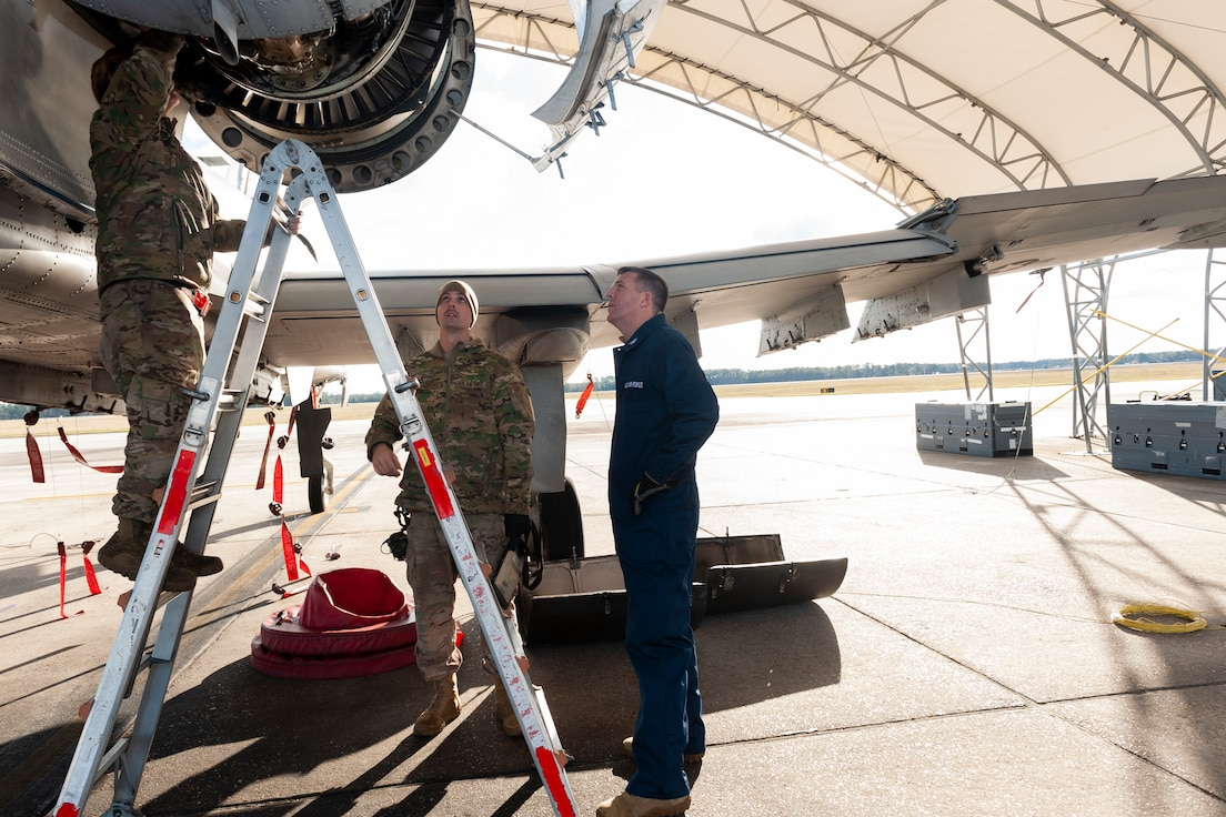 Photo of Airmen showing Col. Walls an engine