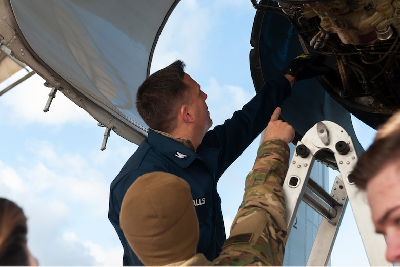 Photo of Airman and Col. Walls pointing at an engine