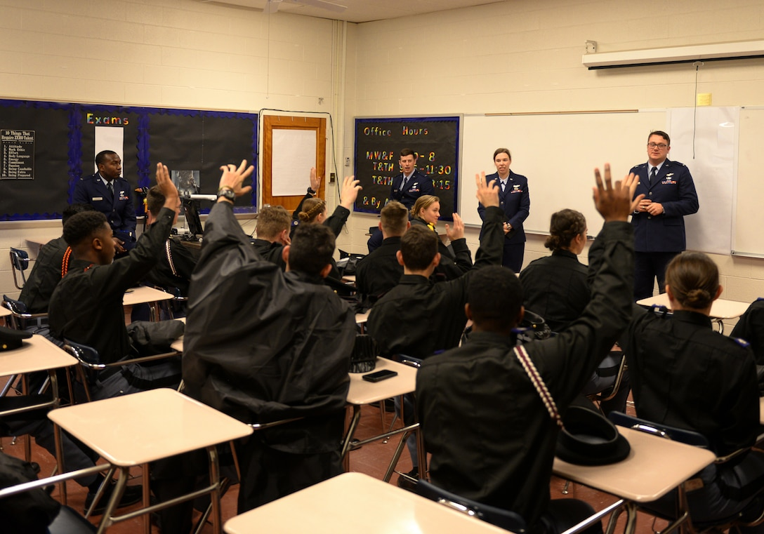 Marion Military Institute cadets raise their hands, while four 14th Flying Training Wing instructor pilots stand in front of them Feb. 10, 2020, at MMI in Marion, Ala. Before raising their hands, the cadets were asked who wanted to be a pilot. (U.S. Air Force photo by Airman Davis Donaldson)