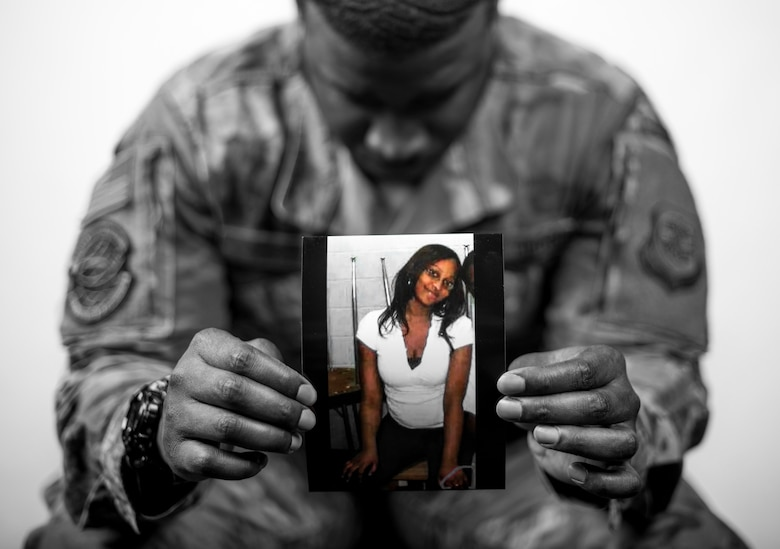 Staff Sgt. Leonard James, 436th Logistic Readiness Squadron Vehicle Maintenance, holds a photo of his late fiancé Mesha. James lost Mesha and his unborn daughter, McKenzie Harmony James, in a 2010 car accident while attending vehicle maintenance technical training.  (U.S. Air Force illustration by Senior Airman Christopher Quail) [image color has been modified for dramatic effect]