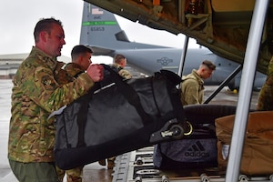 Airmen from the 61st Airlift Squadron load bags onto a C-130J Super Hercules.