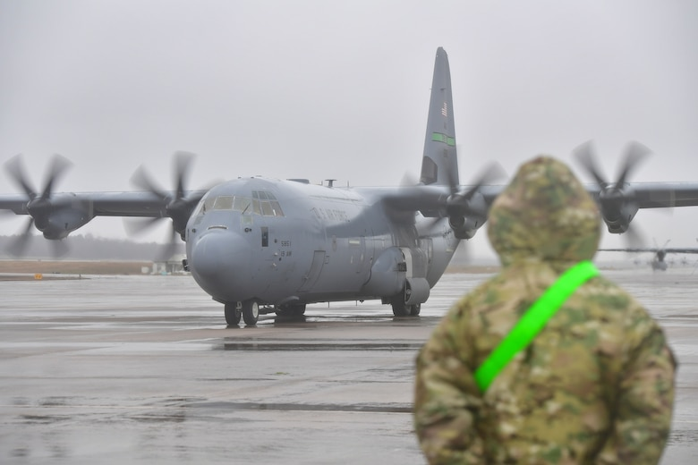 A crew chief from the 19th Aircraft Maintenance Squadron prepares to marshall out a C-130J Super Hercules.