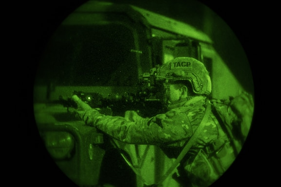 A Tactical Air Control Party specialist from the 148th Air Operations Squadron fires his weapon during night-time training.