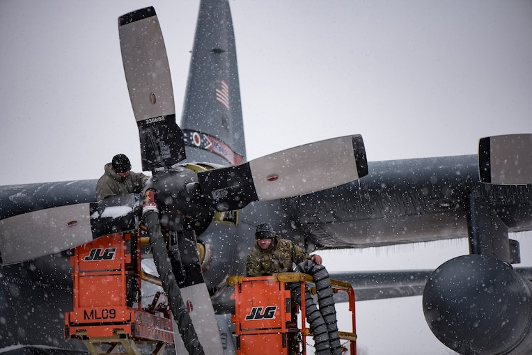 Airmen work on an aircraft as it snows.