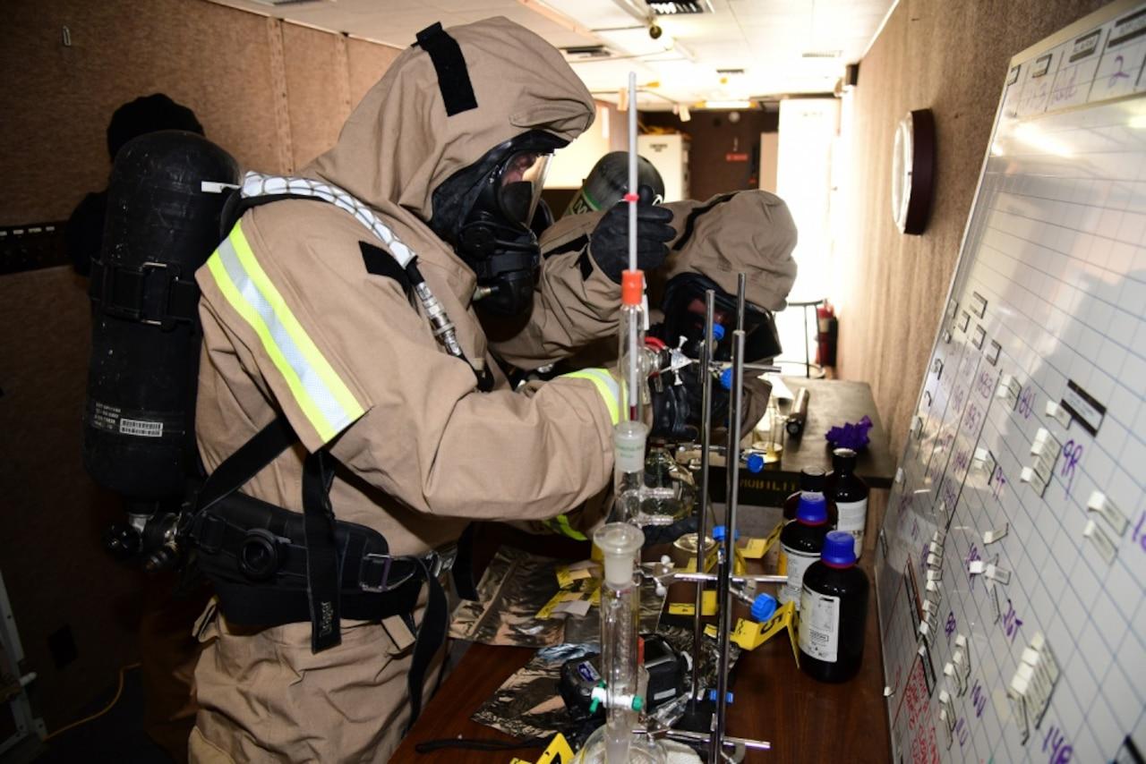 Service members investigate possible contamination.