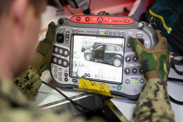 A sailor holds a video monitoring device.