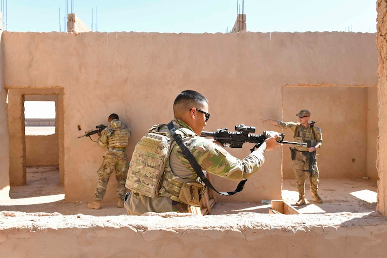 Three airmen hold weapons in an unfinished building.