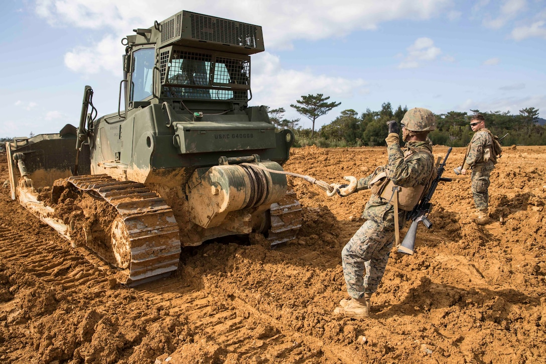 A Marine does a hand signal from behind heavy machinery as another Marine stands by.
