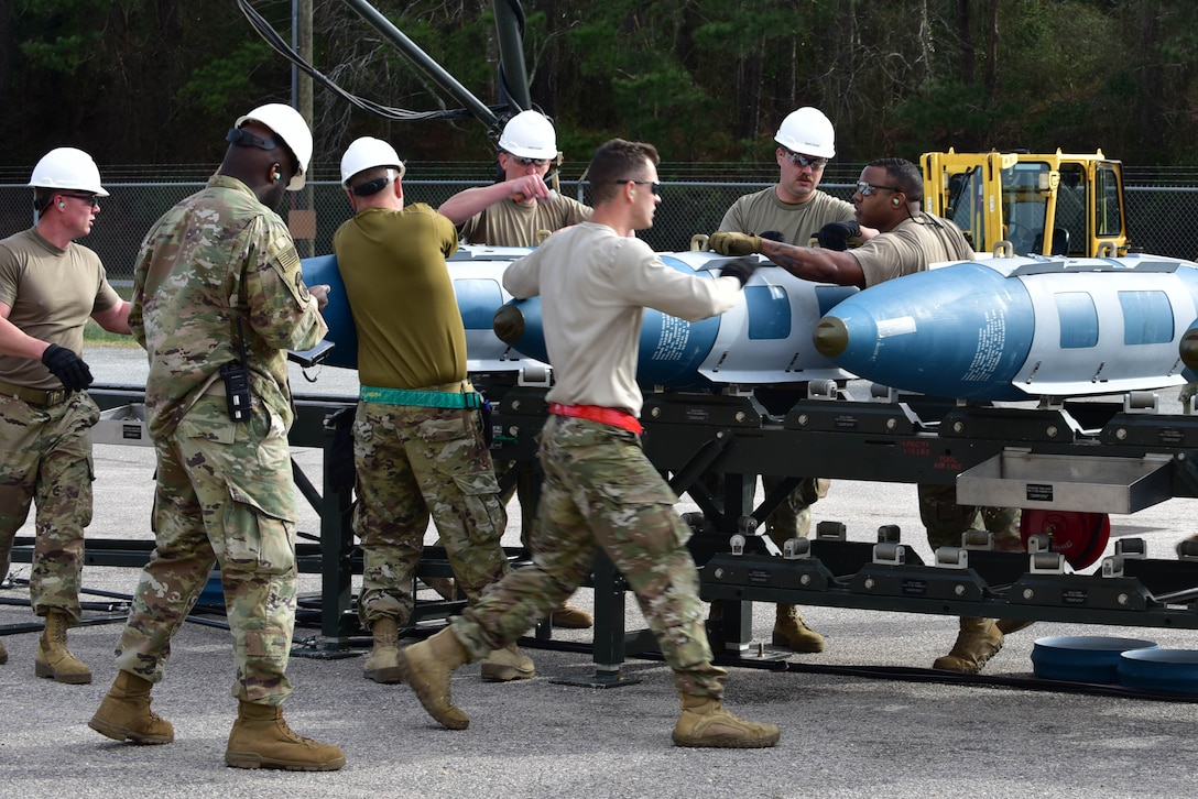 Airmen from the 4th Munitions Squadron install various components onto four guided bomb units during an Air Force Combat Operations Competition qualification.