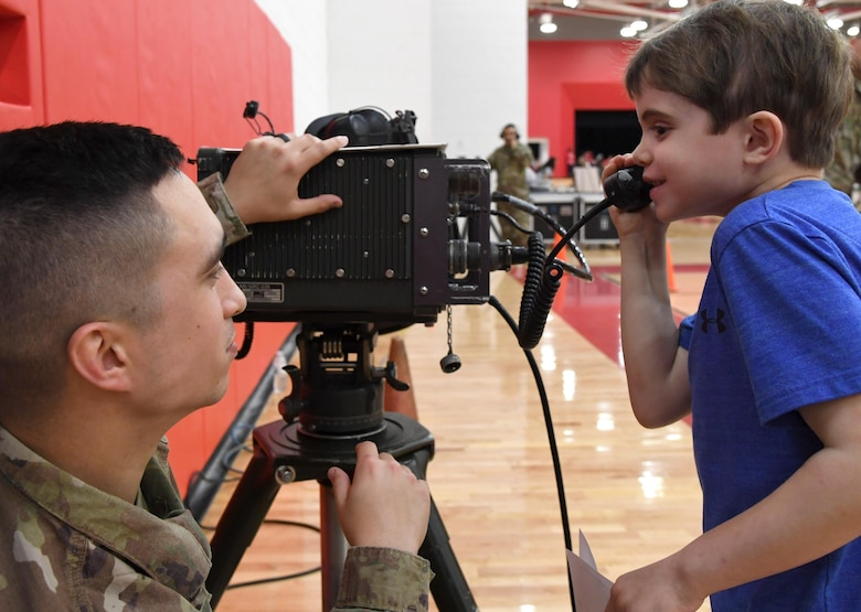 U.S. Air Force Tech. Sgt. John Hoefler, 338th Training Squadron instructor, provides Elijah Foley, North Bay Elementary School student, with a radio frequency communications demonstration during the Biloxi Science, Technology, Engineering and Mathematics Night at the Biloxi Junior High School gymnasium, Biloxi, Mississippi, Feb. 11, 2020. The entire Biloxi school district was invited to the event which promoted STEM. Seven career fields from Keesler's 81st Training Wing and the 81st Training Group participated in the event. (U.S. Air Force photo by Kemberly Groue)
