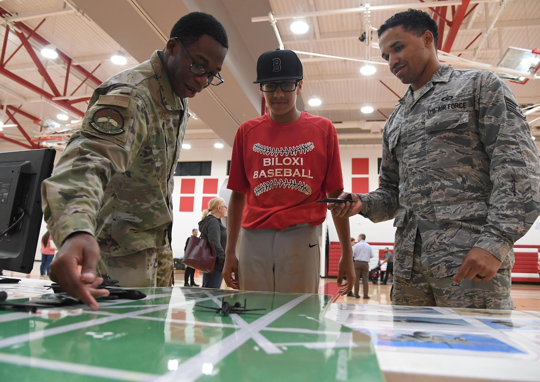 U.S. Air Force Staff Sgts. Nathaniel DeLoatch and LeAnthony Bosserman, 334th Training Squadron instructors, provide Carlos Hurtado, Jr., Biloxi Junior High School student, with an air traffic control training demonstration during the Biloxi Science, Technology, Engineering and Mathematics Night at the Biloxi Jr. High School gymnasium, Biloxi, Mississippi, Feb. 11, 2020. The entire Biloxi school district was invited to the event which promoted STEM. Seven career fields from Keesler's 81st Training Wing and the 81st Training Group participated in the event. (U.S. Air Force photo by Kemberly Groue)