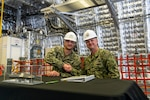 Cmdr. William Dvorak (left) , executive officer, future USS Kansas City (LCS 22) and Cmdr. Kris Netemeyer, littoral combat ship (LCS) program manager's representative Supervisor of Shipbuilding Gulf Coast congratulate each other on the delivery of the 11th Independence variant LCS.