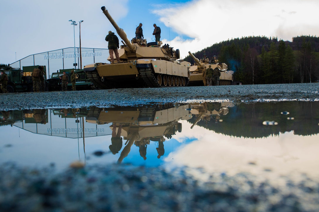 Service members stand atop a tank in a waterlogged dirt parking lot.