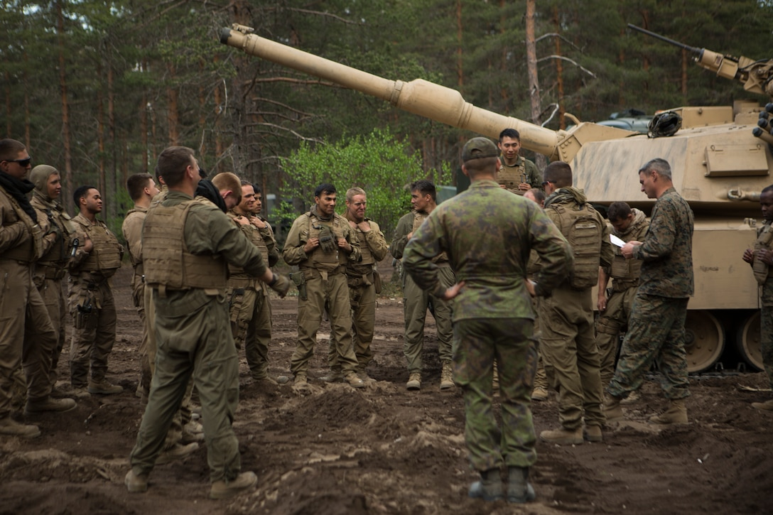 Service members stand near a tank in a forested area.