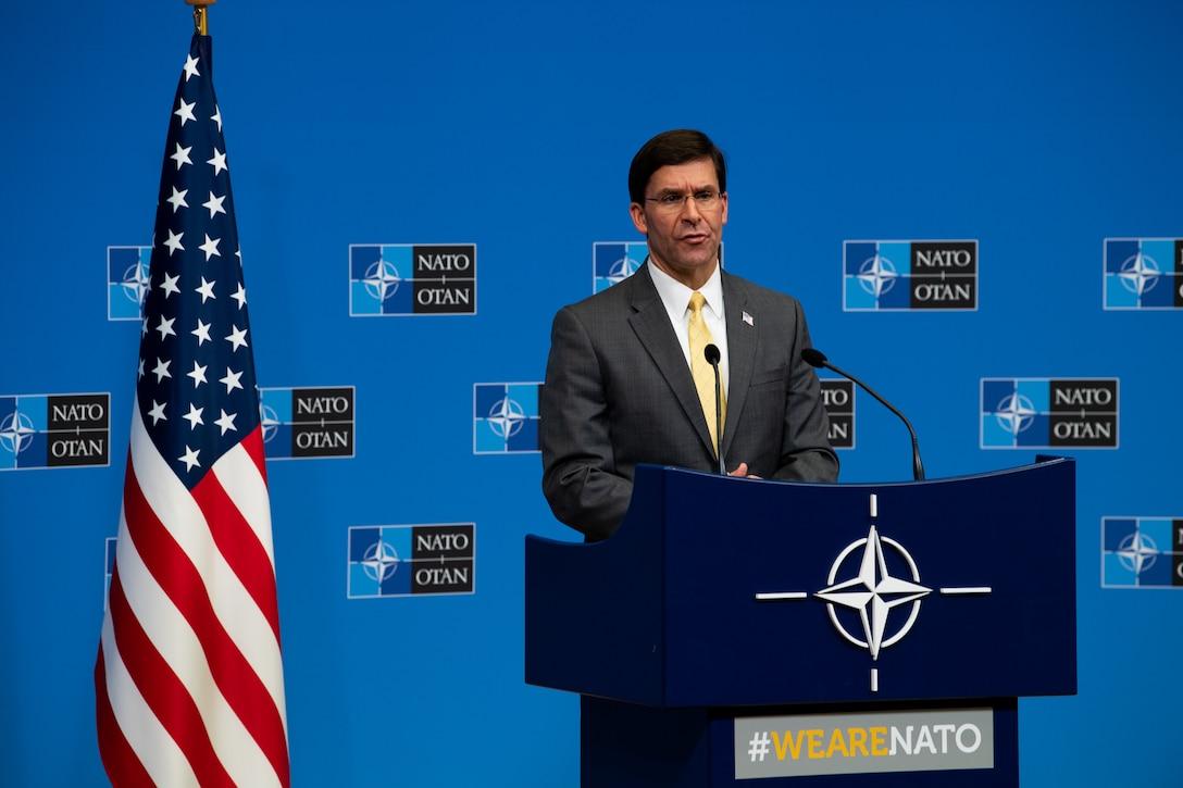 Defense Secretary Dr. Mark T. Esper specks at a podium.