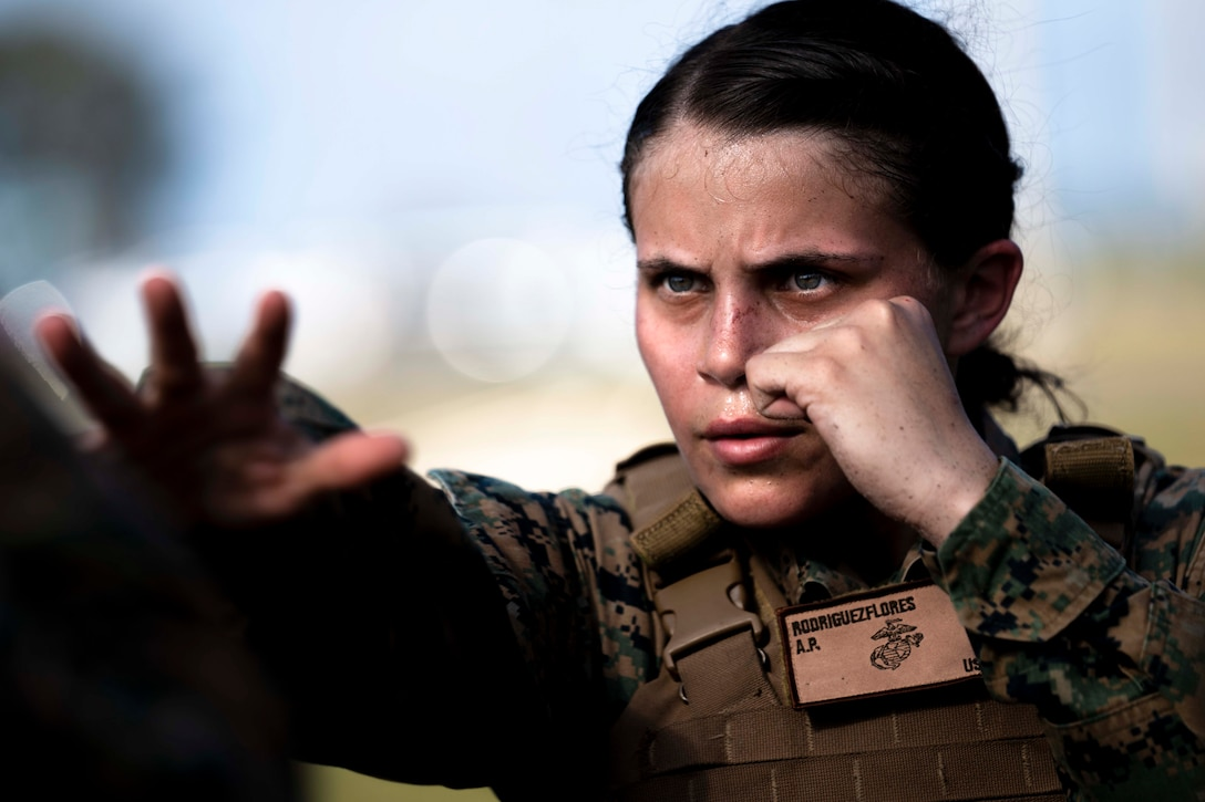 A Marine throws one hand forward while holding the other hand close to her face in a fist.