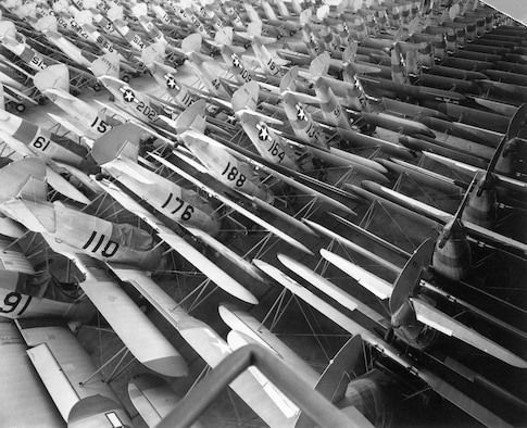 Dozens of PT-13 aircraft are stacked like books, nose-to-nose and tail-to-tail.