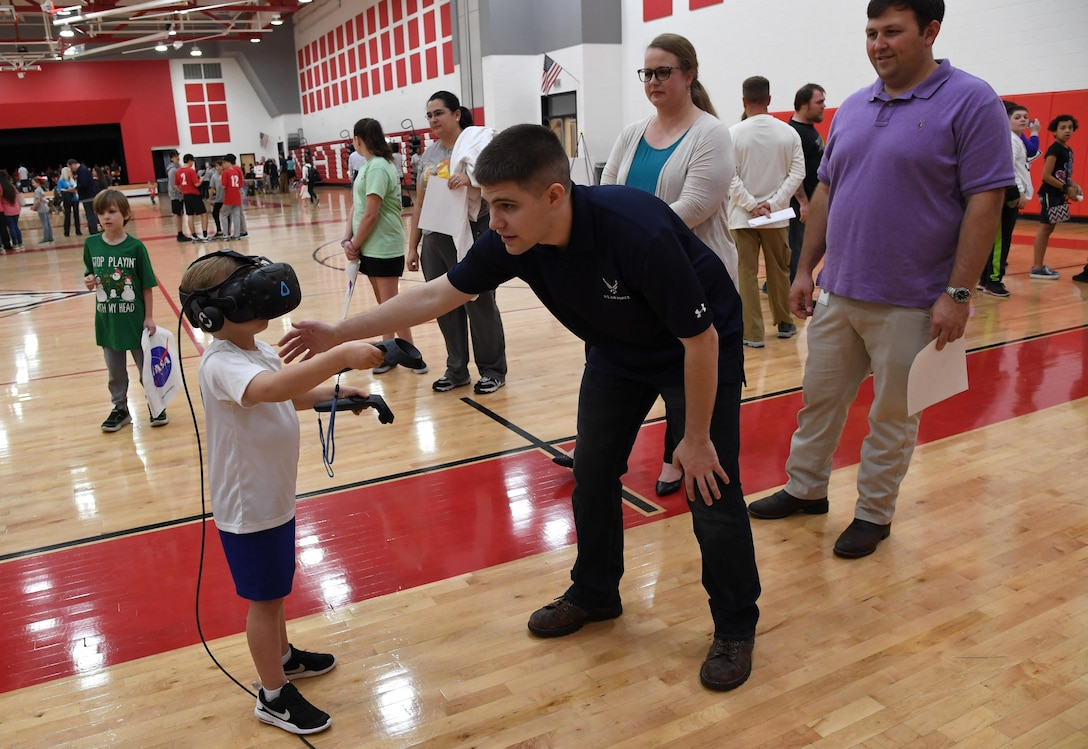 U.S. Air Force Staff Sgt. Brandon McCool, 81st Training Support Squadron interactive multimedia supervisor, provides Jack Carron, North Bay Elementary School student, with a virtual reality demonstration, during the Biloxi Science, Technology, Engineering and Mathematics Night at the Biloxi Junior High School gymnasium, Biloxi, Mississippi, Feb. 11, 2020. The entire Biloxi school district was invited to the event which promoted STEM. Seven career fields from Keesler's 81st Training Wing and the 81st Training Group participated in the event. (U.S. Air Force photo by Kemberly Groue)