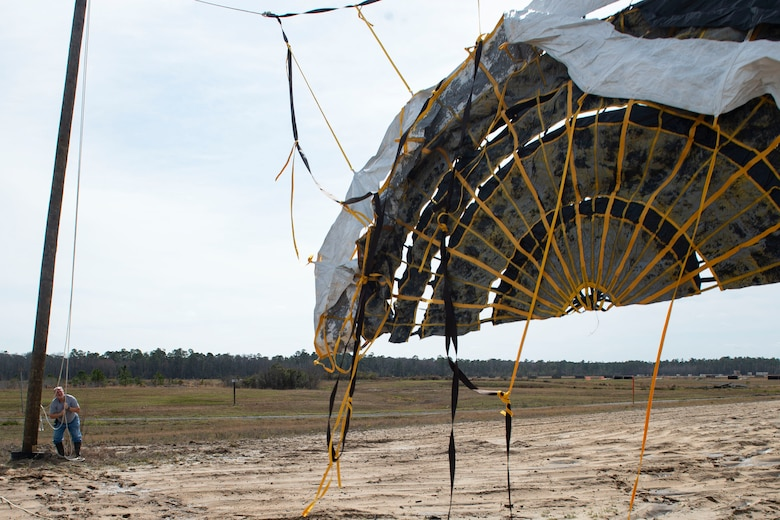 Photo of a range operator hoisting a drogue parachute.