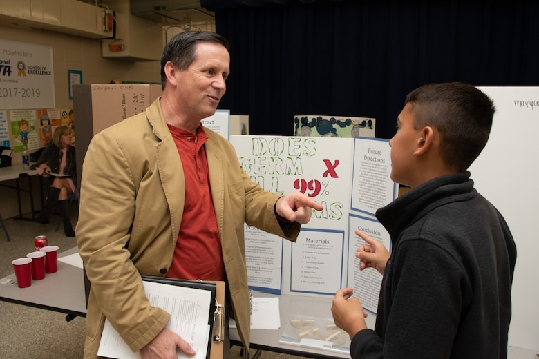 Russ Dunford, who manages strategic plans and integration at Huntsville Center, interviews a sixth-grade student during Monte Sano Elementary School's science fair in Huntsville, Alabama, Jan. 15, 2020.