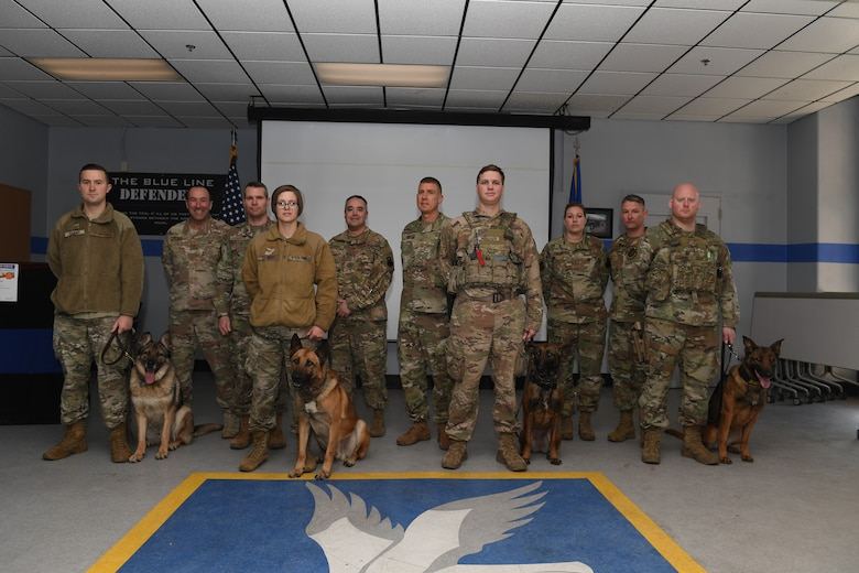 Group photo of military working dogs with their handlers along with others.