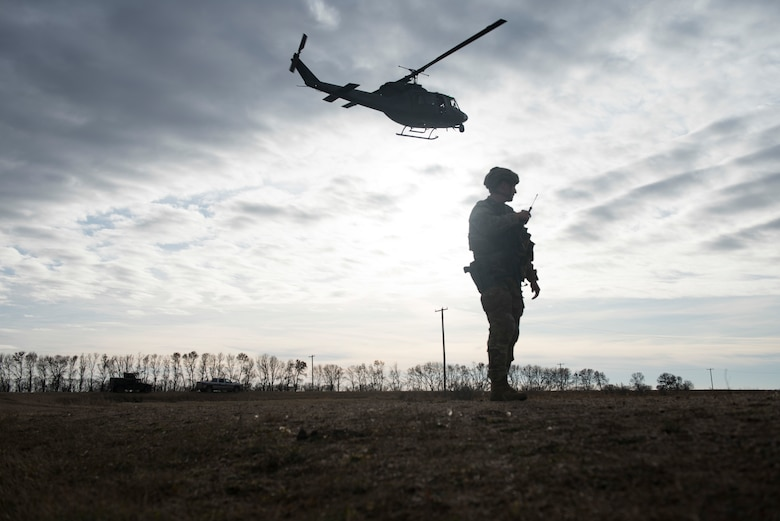 A security forces defender provides ground support guidance for a helicopter landing.