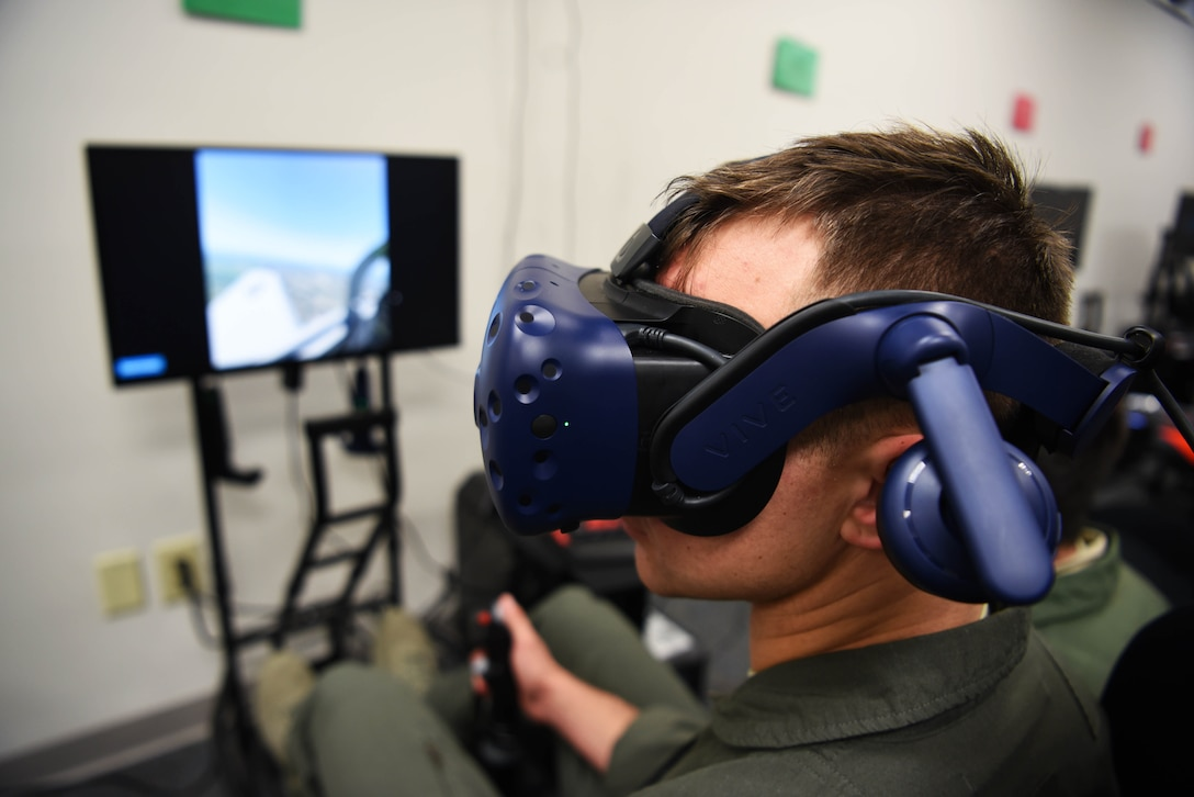 Second Lt. Matthew Demarco, 14th Student Squadron student pilot, looks around with the virtual reality flight simulation equipment strapped on Feb. 11, 2020, on Columbus Air Force Base, Miss. With the help of VR equipment, students see the things they would normally see in an aircraft while being able to follow their procedures as the class instructors provides feedback and grading. (U.S. Air Force photo by Airman 1st Class Jake Jacobsen)