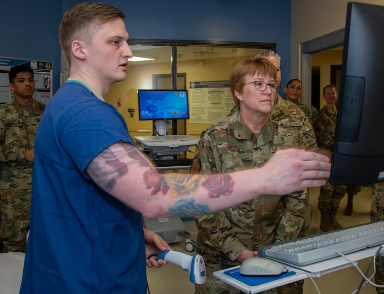 U.S. Air Force Airman 1st Class Trystan Self, left, 60th Inpatient Squadron critical care technician, demonstrates new technology on how information is recorded as Lt. Gen. Dorothy Hogg, Air Force Surgeon General, right, looks on during a tour through the 60th IPTC clinic, David Grant USAF Medical Center at Travis Air Force Base, California, Feb. 10, 2020. Hogg visited with 60th Medical Group Airmen and recognized the positive impact they have on their community through their innovative medical practices. (U.S. Air Force photo by Heide Couch)