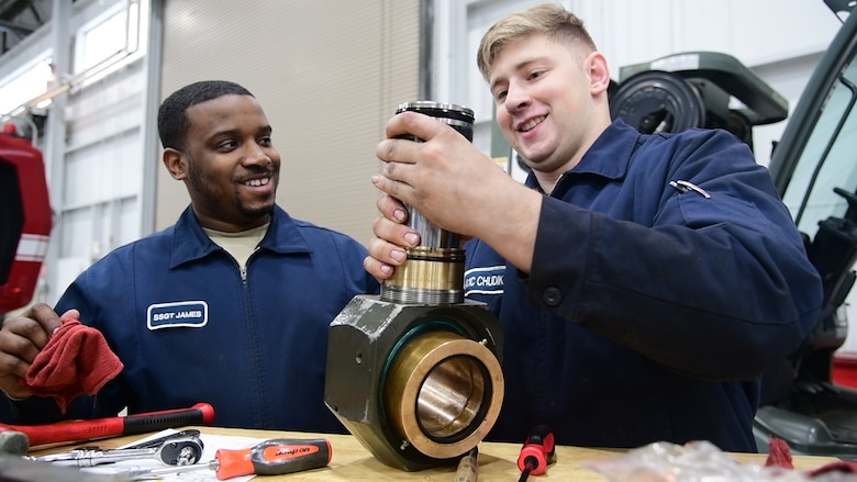 Staff Sgt. Leonard James and Airman First Class Mark Chudik, 436th Logistic Readiness Squadron Vehicle Maintenance, repair a hydraulic component for a k-loader at Dover Air Force Base, Del., on January 29, 2020. James lost his fiancé and unborn daughter in a 2010 car accident while attending vehicle maintenance technical training. (U.S. Air Force photo by Tech. Sgt. Laura Beckley).