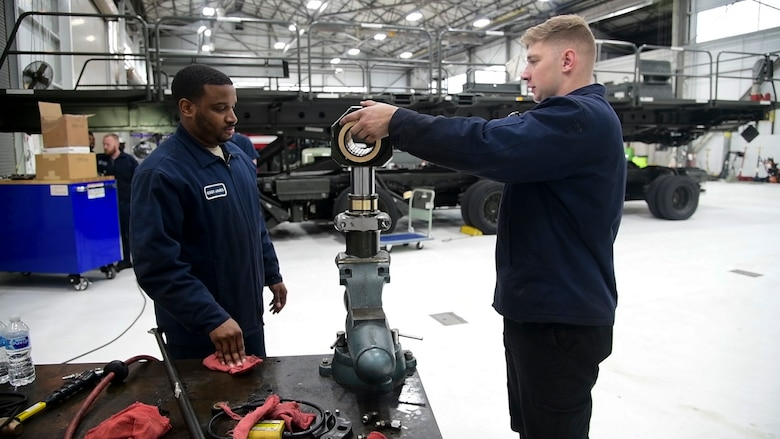 Staff Sgt. Leonard James (left) and Airman 1st Class Mark Chudik, 436th Logistic Readiness Squadron vehicle maintenance, repair a hydraulic component for a k-loader at Dover Air Force Base, Del., Jan. 29, 2020. James lost his fiancé and unborn daughter in a 2010 car accident while attending vehicle maintenance technical training. (U.S. Air Force photo by Tech. Sgt. Laura Beckley).