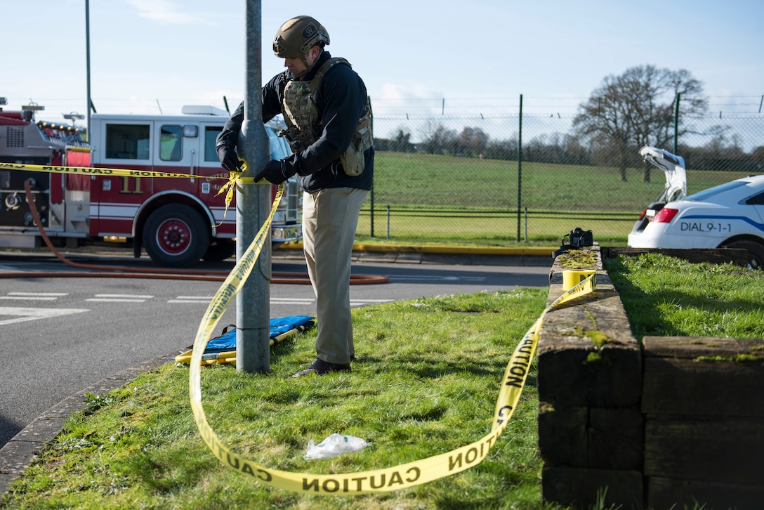 U.S. Air Force Staff Sgt. Kirk Clark, 422nd Security Forces Squadron investigator, ties caution tape around simulated car bomb location during the 501st Combat Support Wing Readiness Exercise 20-01 at RAF Croughton, England, Feb. 12, 2020. The exercise tested the wing's preparedness and response capabilities to an emergency situation. (U.S. Air Force photo by Airman 1st Class Jennifer Zima)