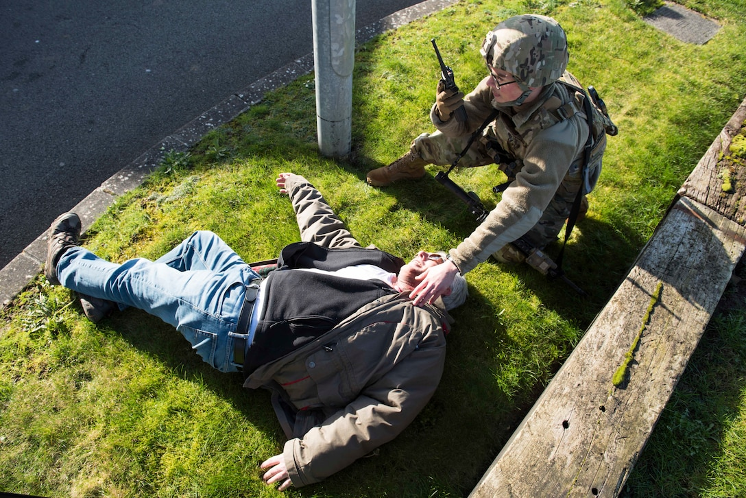 U.S. Air Force Airman 1st Class Graham Stubblefield, 422nd Security Forces Squadron installation entry controller, calls for backup to assist a simulated casualty during the 501st Combat Support Wing Readiness Exercise 20-01 at RAF Croughton, England, Feb. 12, 2020. The exercise tested the wing's preparedness and response capabilities to an emergency situation. (U.S. Air Force photo by Airman 1st Class Jennifer Zima)