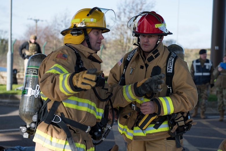 Phillip Semper, 422nd Civil Engineer Squadron firefighter, and Michael Davy, 422nd CES firefighter crew chief, discuss the next steps during the 501st Combat Support Wing Readiness Exercise 20-01 at RAF Croughton, England, Feb. 12, 2020. The exercise tested the wing's preparedness and response capabilities to an emergency situation. (U.S. Air Force photo by Airman 1st Class Jennifer Zima)