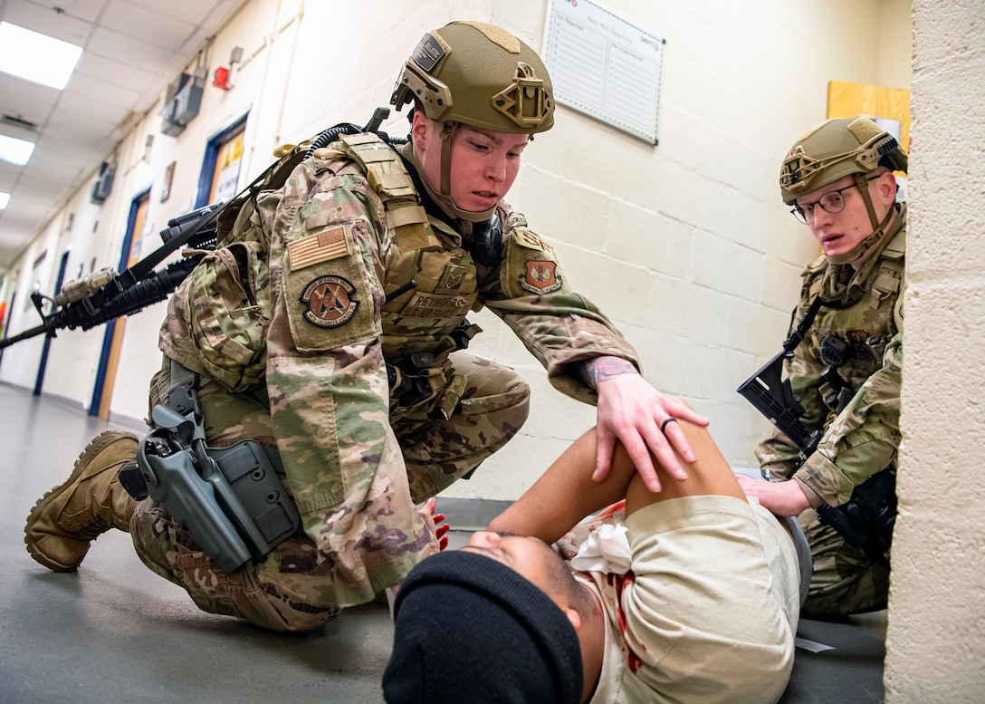 Staff Sgt. Chelsea Reynolds, (left) 423d Security Forces Squadron flight sergeant, and Senior Airman Wyatt White, (right), tend to a simulated victim during a readiness exercise, at RAF Molesworth, England, Feb. 11, 2020. The exercise tested the wing's preparedness and response capabilities to an emergency situation. (U.S. Air Force photo by Senior Airman Eugene Oliver)