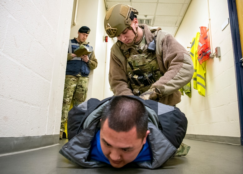 Senior Airman Dustin Kluge, (center), 423d Security Forces Squadron Emergency center controller, apprehends a simulated suspect during a readiness exercise, at RAF Molesworth, England, Feb. 11, 2020. The exercise tested the wing's preparedness and response capabilities to an emergency situation. (U.S. Air Force photo by Senior Airman Eugene Oliver)