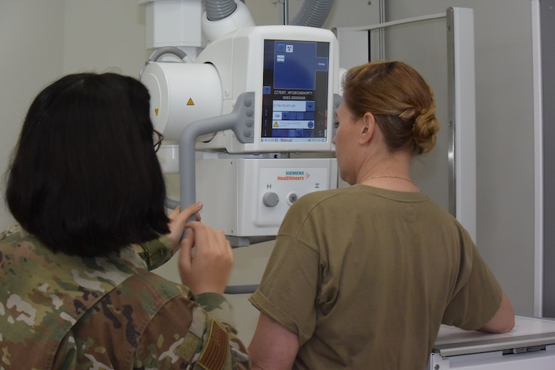 two women next to an x-ray machine