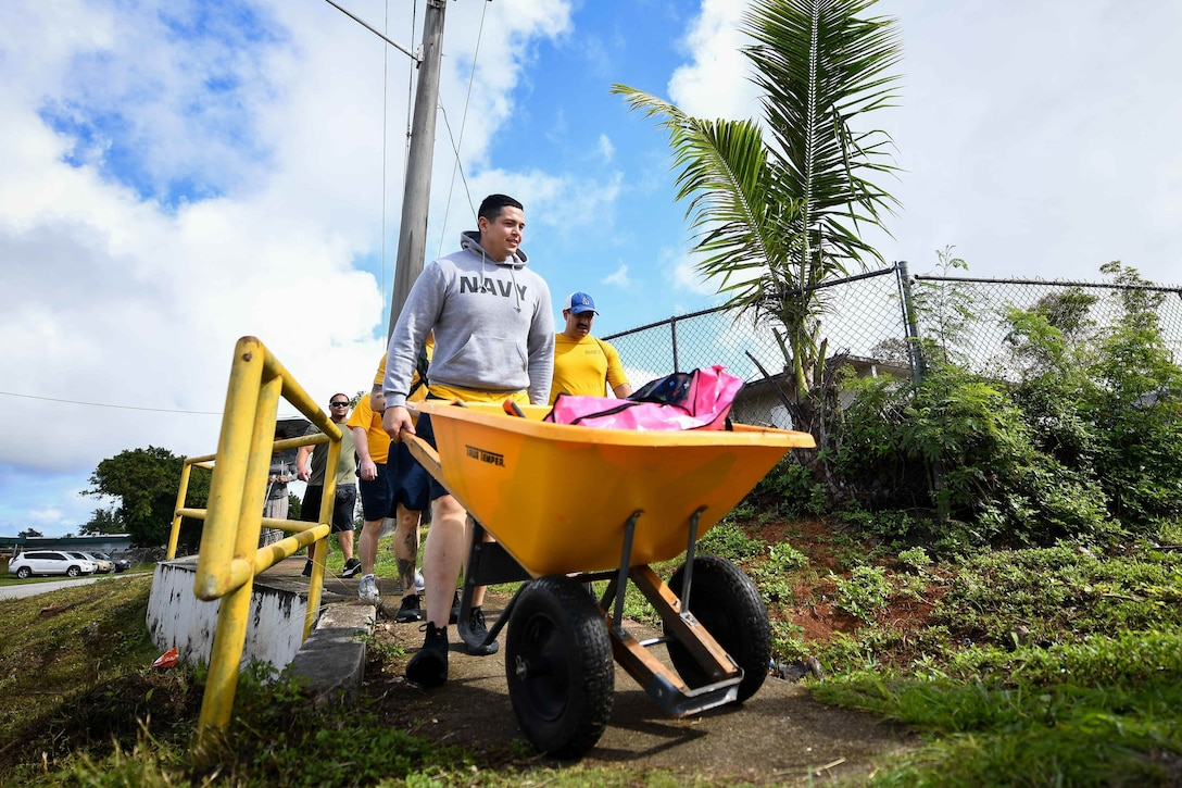 A sailor pushes a large yellow wheelbarrow at a park as other service members in civilian clothes walk behind him.