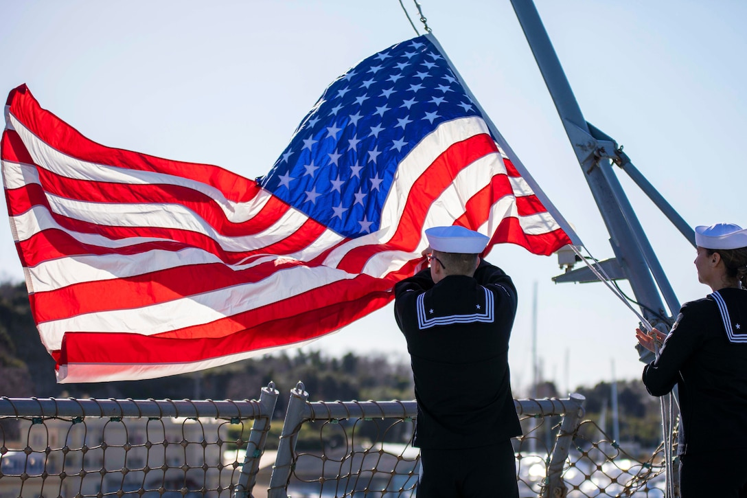 Two sailors adjust an American flag.
